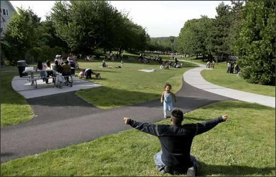 Emily Isabella Ramirez, 3, and Ricardo Pena enjoy Columbia City's park on June 27. While the park was redone, and much of Columbia City revitalized, elsewhere in Rainier Valley there is controversy between neighborhood planning and what the city wants to happen. Photo: Meryl Schenker/Seattle Post-Intelligencer