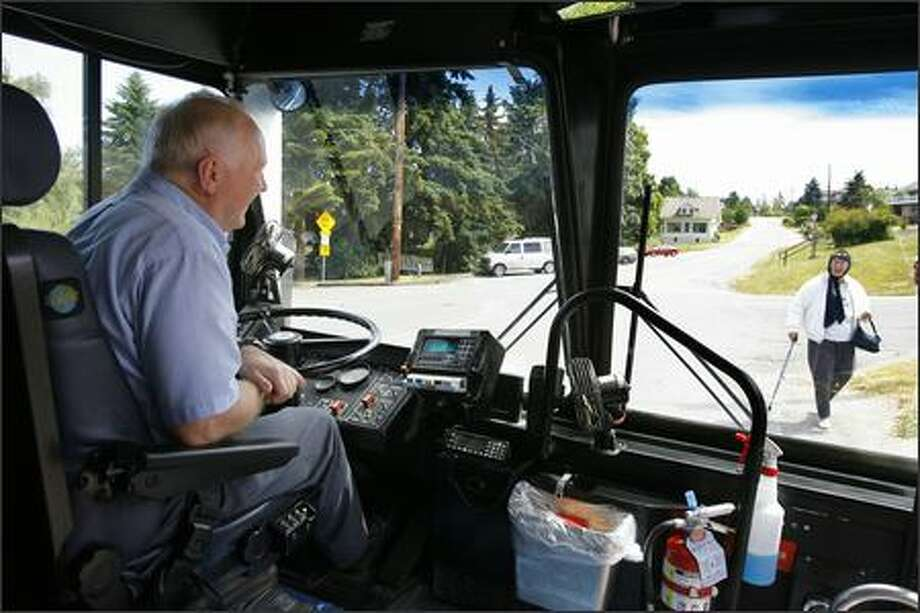 Island Transit bus driver Hank Trusler waits for rider Lillie McCurik in Freeland on Whidbey Island on Monday. Trusler had closed his door and was about to pull away after letting off a passenger when he saw McCurik headed to the stop. Island Transit is supported by local, federal and state tax money, and has never charged a fare. Photo: Gilbert W. Arias/Seattle Post-Intelligencer