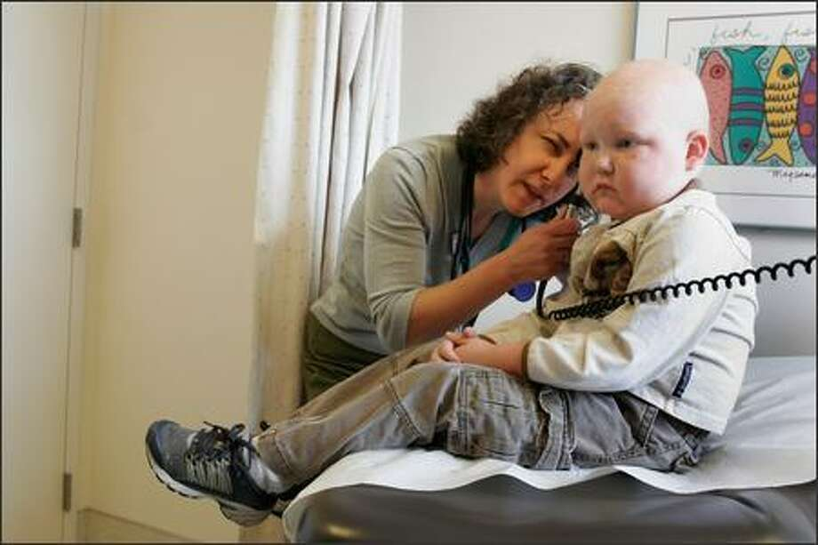Nurse Laura Eisenberg examines Greg Worley before another round of chemo at Children's Hospital. The redhead is enrolled in a research trial to fight his leukemia. Photo: Meryl Schenker/Seattle Post-Intelligencer