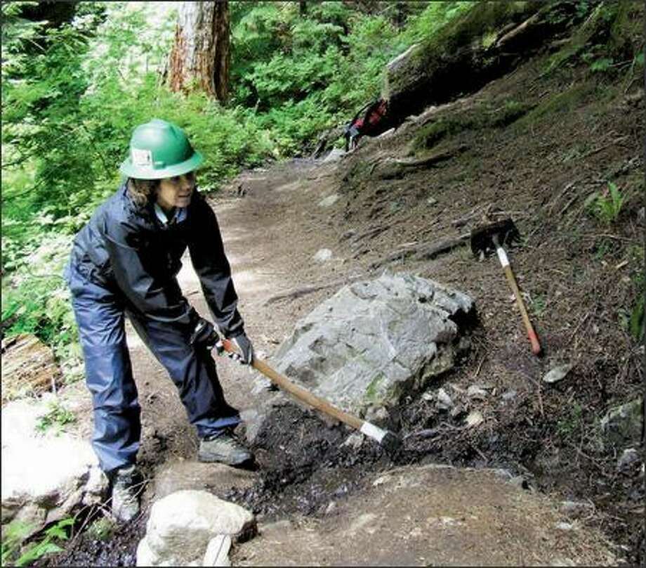 Caroline Whiteoak puts her back into clearing a drainage ditch on the Denny Creek Trail. Whiteoak is a Seattle resident and a member of The Mountaineers. Photo: KAREN SYKES