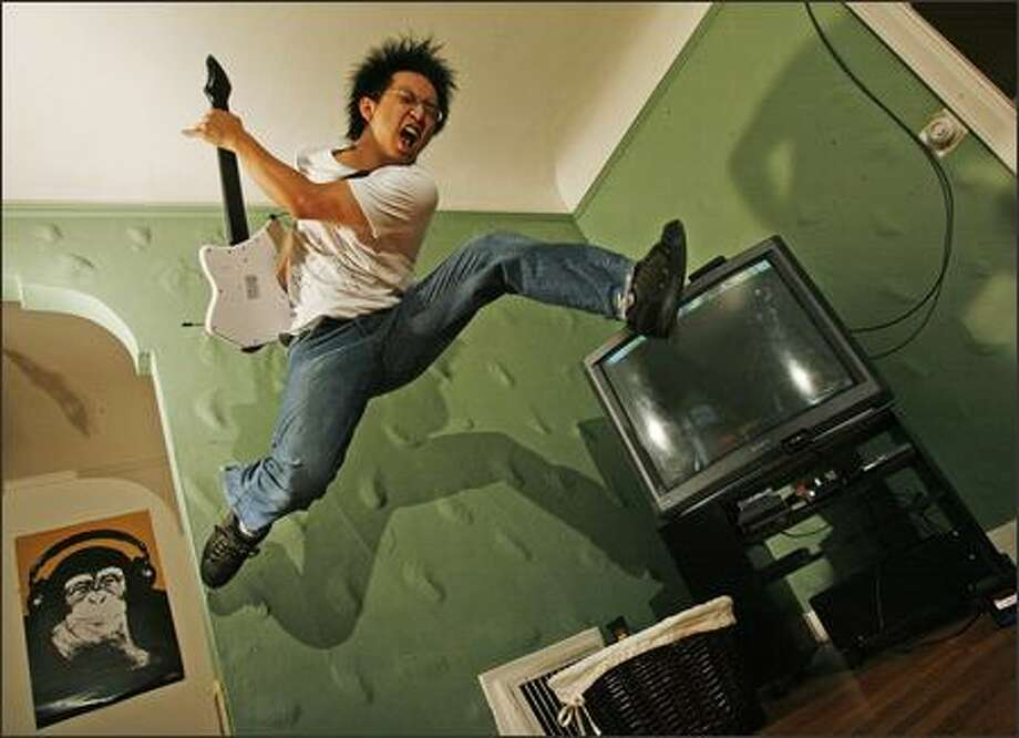 Freddie Wong demonstrates the energy he used to win the World Series of Video Games as plays a plastic guitar along with Xbox game Guitar Hero II. Photo: Grant M. Haller/Seattle Post-Intelligencer