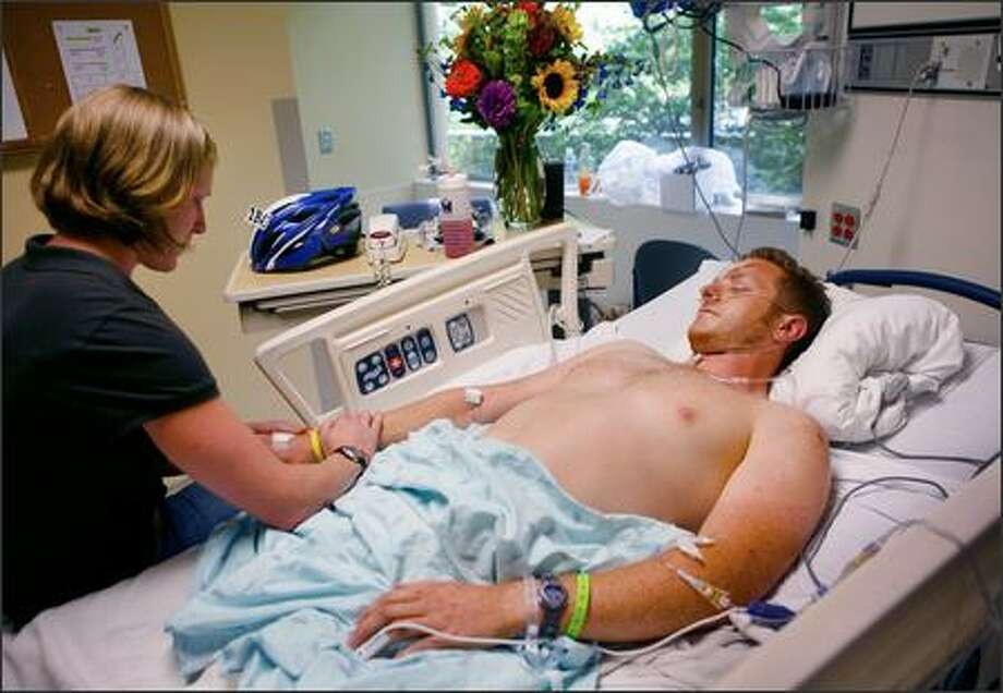 Gerald Marvin visits with girlfriend Amber Brinkman Monday after a car hit him on his ride in the Seattle to Portland bike marathon. Photo: / Associated Press