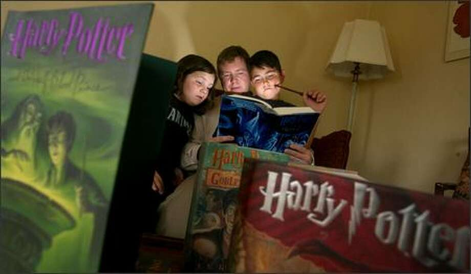 "Chance Hunt and his 10-year-old son John, complete with magic wand, have read the ""Harry Potter"" books together. Here, 9-year-old sister Olivia joins in. Photo: Scott Eklund/Seattle Post-Intelligencer"