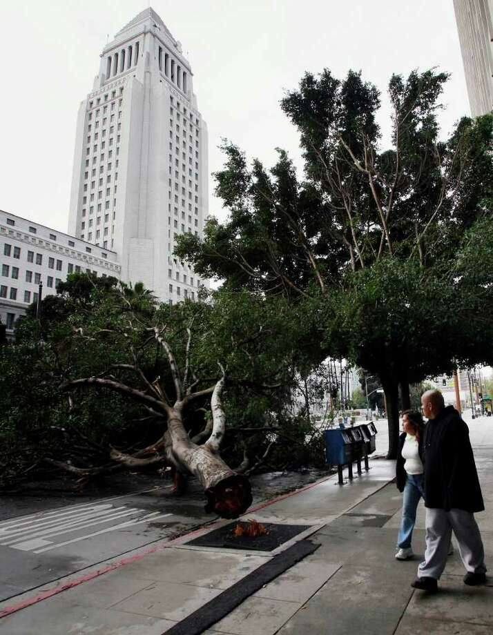 Pedestrians walk past a fallen tree near the Los Angeles City Hall after a storm swept through southern California on Monday, March 21, 2011. The weather was moving out of the region and flood advisories were canceled for Los Angeles County, but the weather service warned that debris flows and flash flooding in some areas were still possible. (AP Photo/Nick Ut) Photo: Nick Ut