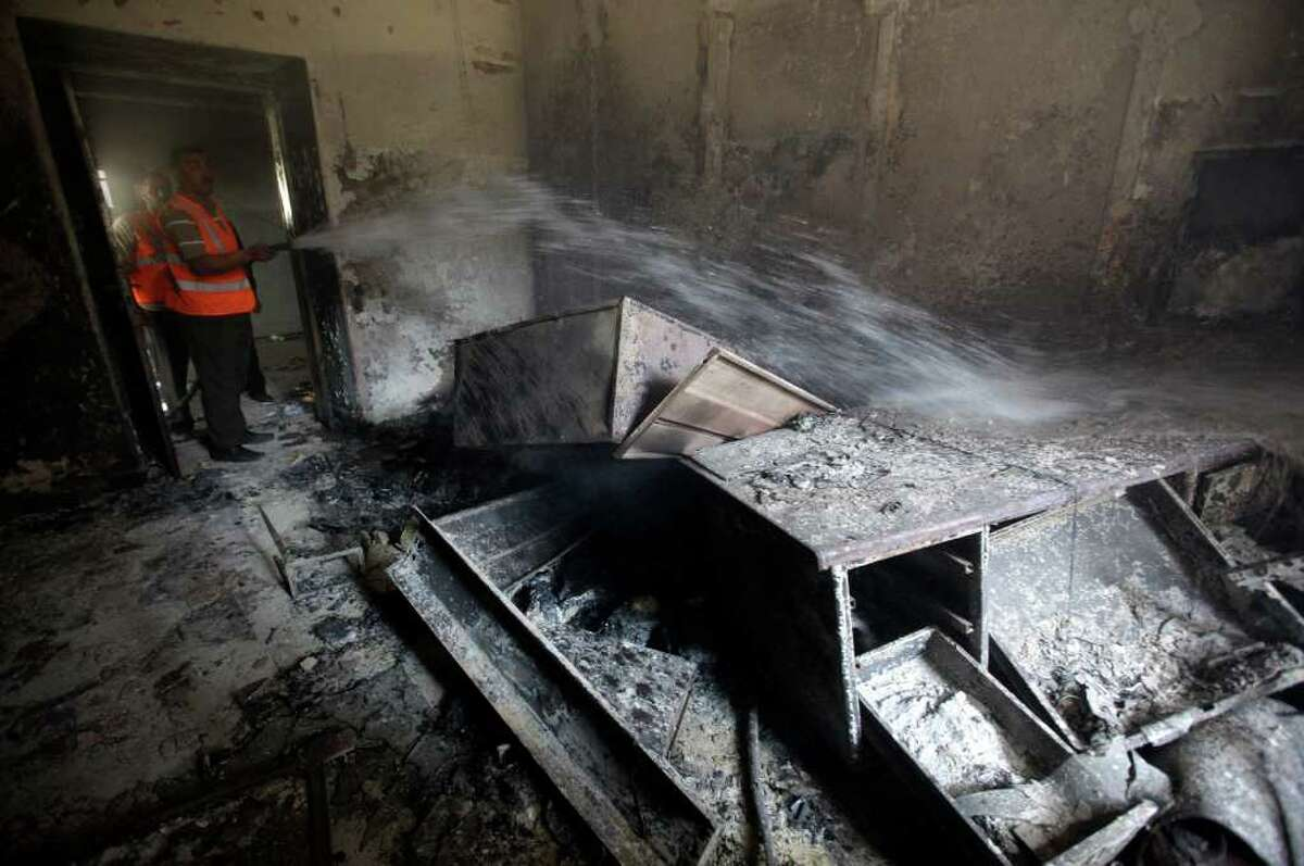 A Syrian municipality worker extinguishes a burned court room that was set on fire by Syrian anti-government protesters, in the southern city of Daraa, Syria, Monday March 21, 2011. Mourners chanting