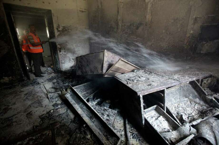 "A Syrian municipality worker extinguishes a burned court room that was set on fire by Syrian anti-government protesters, in the southern city of Daraa, Syria, Monday March 21, 2011. Mourners chanting ""No more fear!"" have marched through a Syrian city where anti-government protesters had deadly confrontations with security forces in recent days. The violence in Daraa, a city of about 300,000 near the border with Jordan, was fast becoming a major challenge for President Bashar Assad, who tried to contain the situation by freeing detainees and promising to fire officials responsible for the violence. (AP Photo/Hussein Malla) Photo: Hussein Malla / AP"