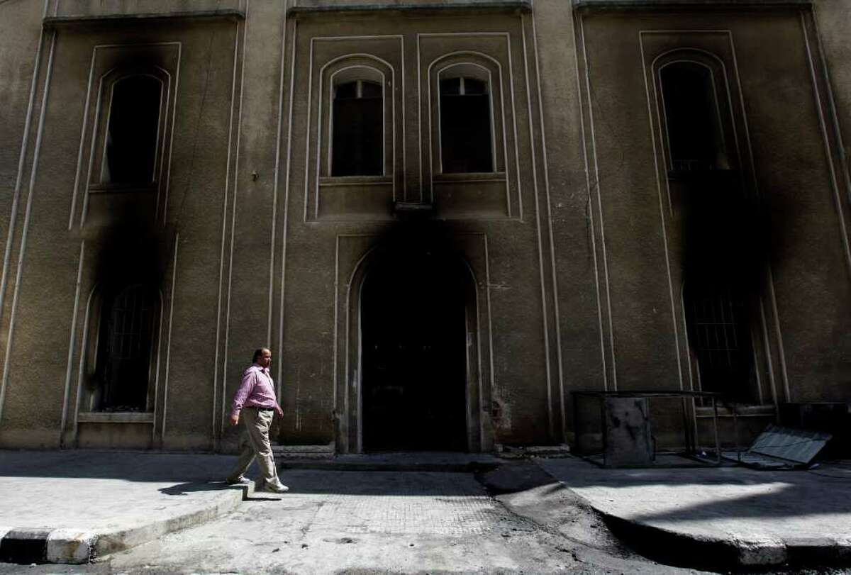 A Syrian man walks next to the burned court building that was set on fire by Syrian anti-government protesters, in the southern city of Daraa, Syria, on Monday March 21, 2011. Mourners chanting