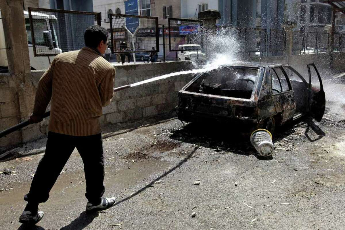 A Syrian municipality worker sprays water at a burnt car that was set on fire by Syrian anti-government protesters, in the southern city of Daraa, Syria, Monday March 21, 2011. Mourners chanting