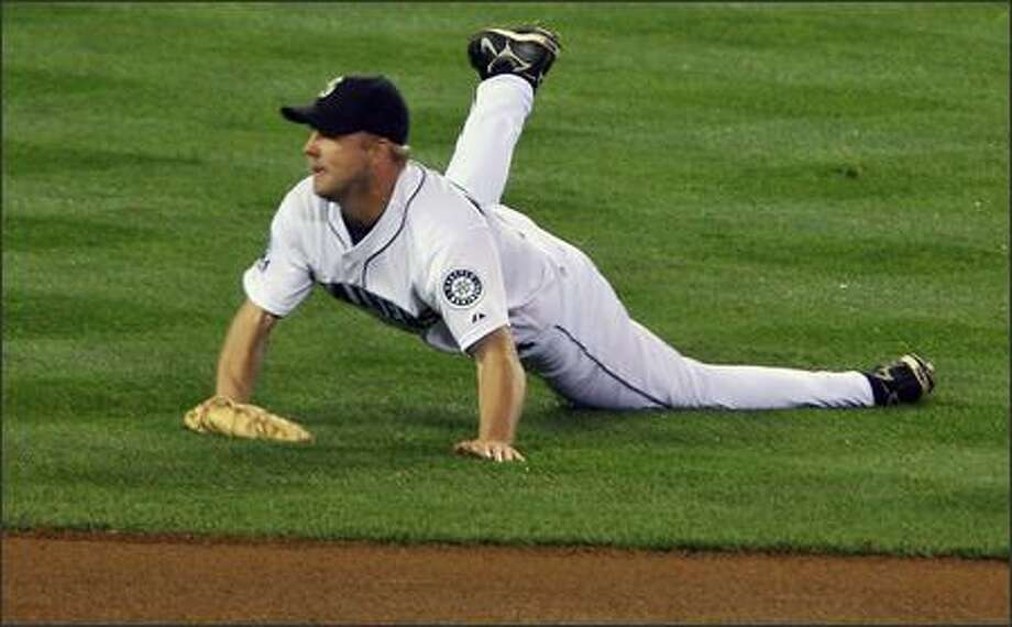 Jarrod Washburn falls to the turf after flipping a toss to first to put out Baltimore's Kevin Millar in the fourth inning. Washburn had deflected Millar's line drive toward first and had to chase it down. Photo: Mike Urban/Seattle Post-Intelligencer