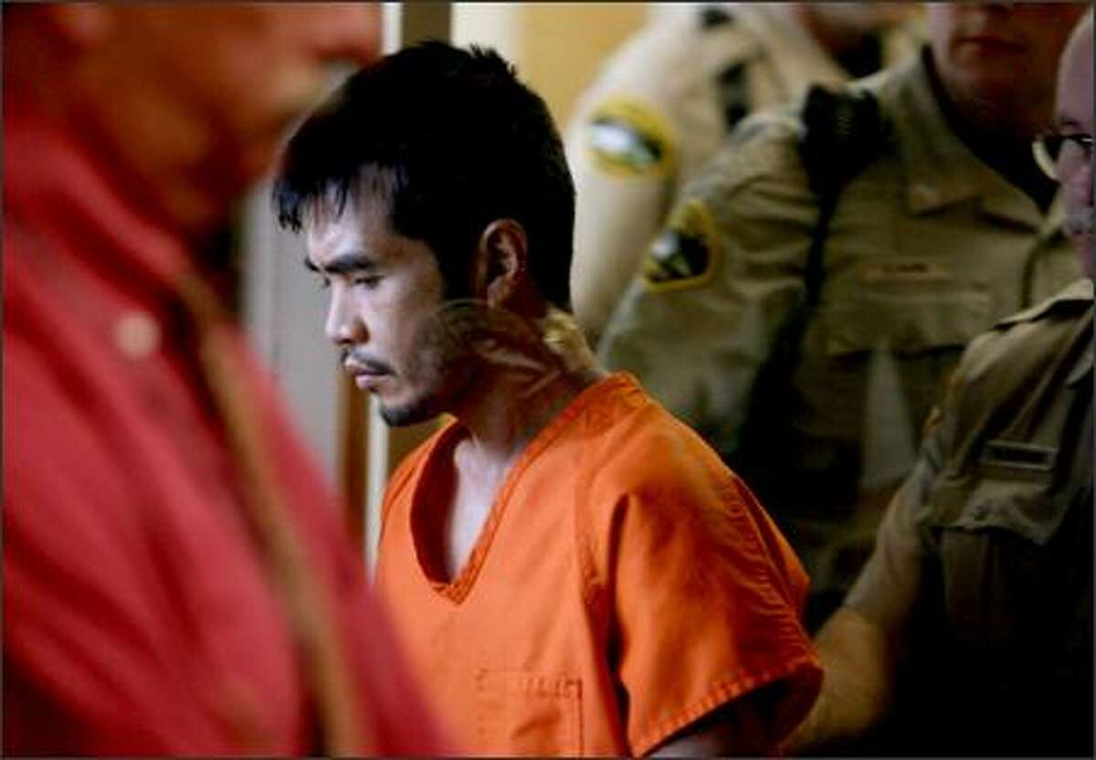Terapon Dang Adhahn is led out of court Thursday, after his arraignment before Judge John Hickman in which Pierce County prosecutors filed 12 felony kidnapping and rape charges against him. On Adhahn's neck is the reflection of a glass partition.