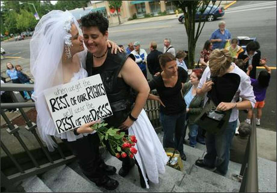 Amanda Swarr, on left, and T Steele of Tacoma wait their turn to register as domestic partners in Olympia, WA on Monday, July 23, 2007. Steele is wearing the lower part of a wedding dress worn by Swarr. The severed dress symbolizes that a domestic partnership does not equal the rights of a marriage. Photo: Dan DeLong/Seattle Post-Intelligencer