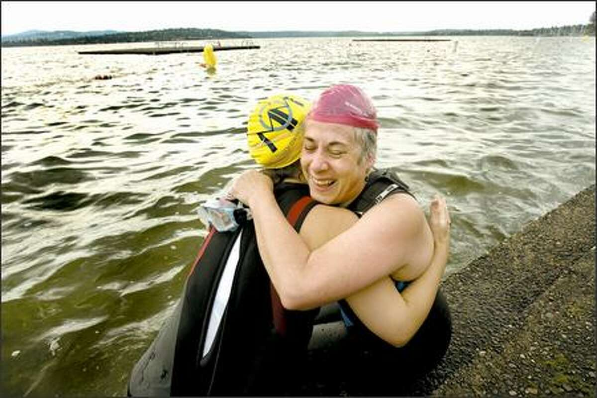 After completing the Lake Washington practice course on Saturday, Barbara Oswald, right, hugs Veronica Smith, her volunteer guide during the swim. Oswald, who lost her sight as an infant, is training for the Danskin 2007 Women's Triathlon on Aug. 19, when she'll do a half-mile swim, 12-mile bike ride and 3.1-mile run.