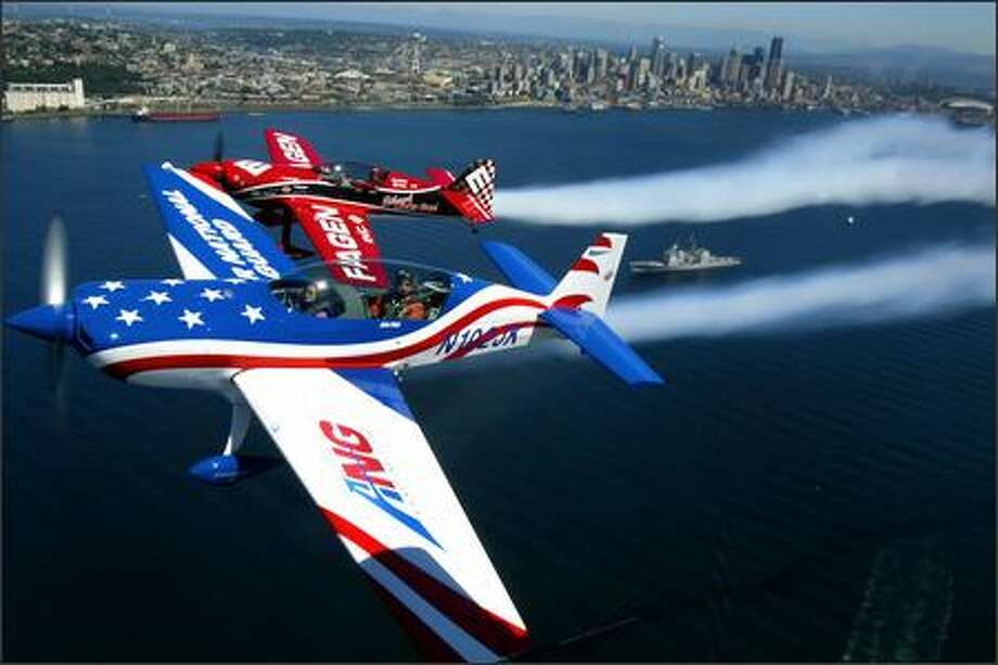 John Klatt, foreground, and his Staudacher S-300D, and Greg Poe and his Fagen MX-2 fly in formation over downtown Seattle and the incoming U.S. Navy fleet on Wednesday in preparation for Seafair. Photo: Joshua Trujillo/Seattle Post-Intelligencer