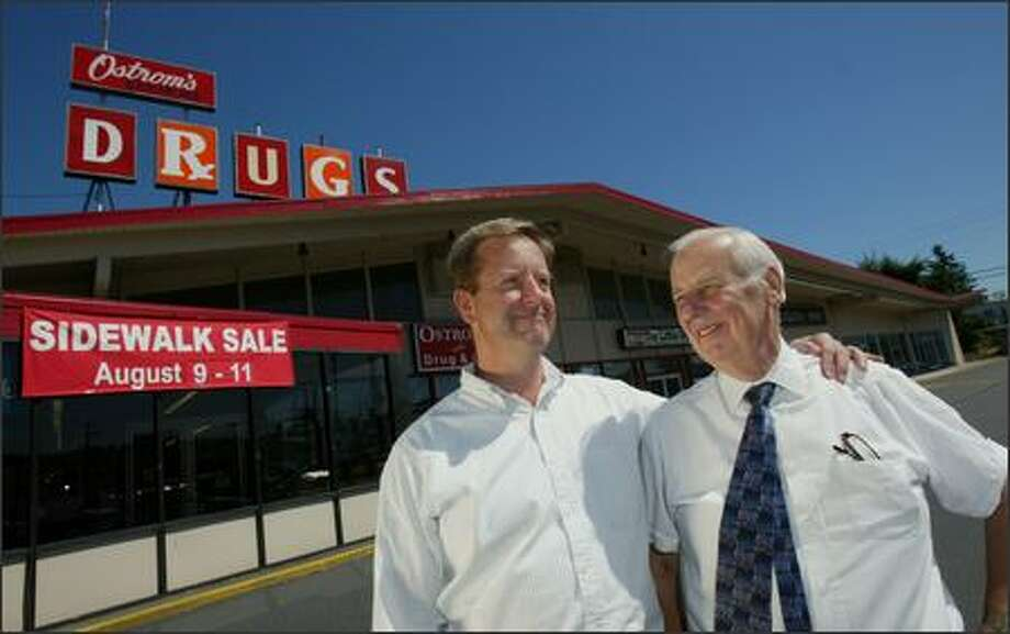 Todd Ramsey, left, stands beside his father Dick Ramsey in front of their store, Ostrom's Pharmacy. The store, a fixture of Kenmore for 44 years, is being pushed out by new development; but the owners have found a new location just 4 blocks away. Photo: Karen Ducey/Seattle Post-Intelligencer