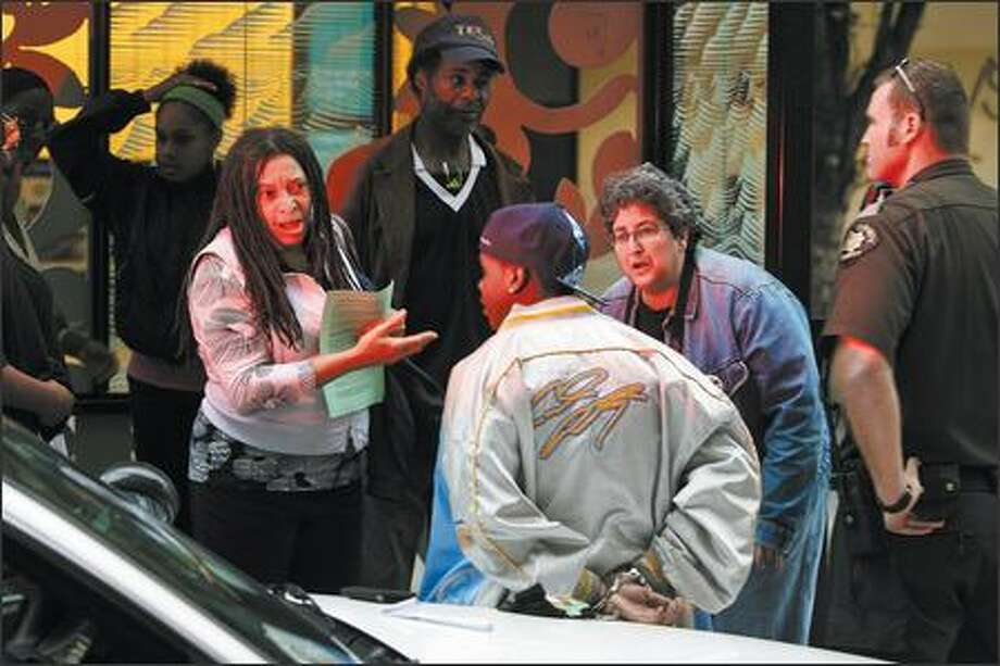 Their faces illuminated by a squad car's flashing lights, Patricia Tinnermon, left, and Peggy Wolf of the Black-on-Black Crime Community Coalition offer support Tuesday to a man identified as Dante arrested for spitting at Third Avenue and Pine Street. Photo: Mike Urban/Seattle Post-Intelligencer