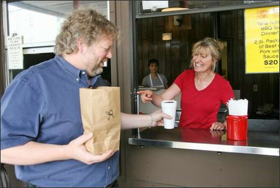 "Debra Wise serves an order of beef barbecue to one of her regulars: celebrated Seattle chef Tom Douglas. Wise said that last year one of Douglas' assistants called to order 100 of Pecos' holiday gift certificates. ""I thought she was joking; I don't read the papers, I didn't know who Tom Douglas was,"" Wise said. Then she looked him up on the Internet and recognized his face. ""I only knew him as one of my regulars who's been coming here since day one."" Photo: Mike Urban/Seattle Post-Intelligencer"