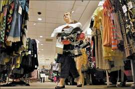 Caitlin Coggeshall walks towards the dressing room during a shopping session, Wednesday in a Nordstrom store in Seattle. Most clothing store chains in the United States have recently come out with their new back-to-school collections.