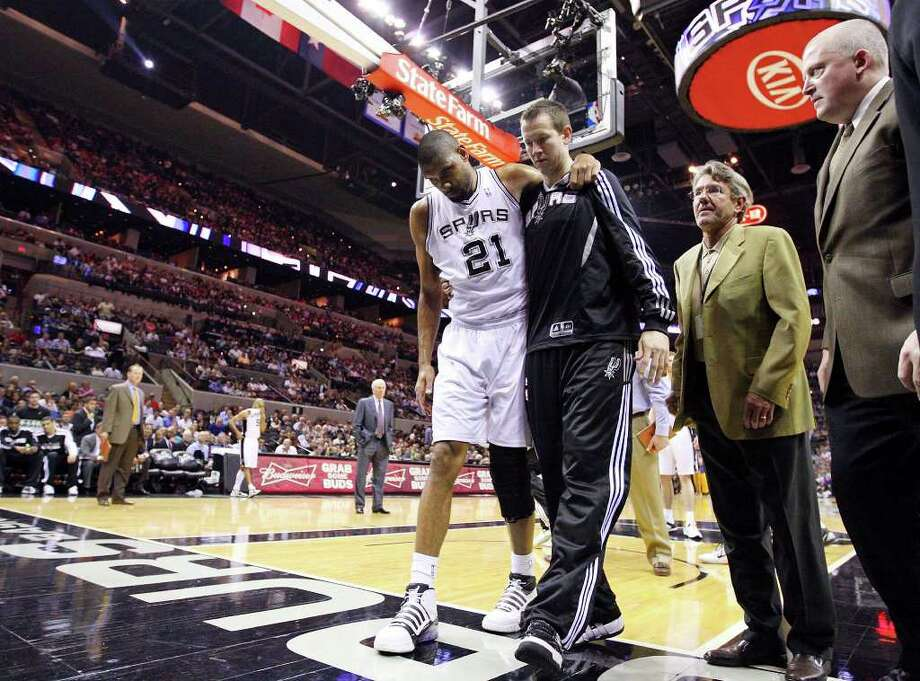 FOR SPORTS - Spurs' Tim Duncan is helped off the court by teammate Steve Novak after he sprained his left ankle during first half action against the Warriors Monday March 21, 2011 at the AT&T Center.  (PHOTO BY EDWARD A. ORNELAS/eaornelas@express-news.net) / SAN ANTONIO EXPRESS-NEWS NFS