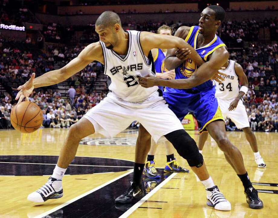 FOR SPORTS - Spurs' Tim Duncan grabs for a loose ball against  Warriors' Ekpe Udoh during first half action Monday March 21, 2011 at the AT&T Center.  (PHOTO BY EDWARD A. ORNELAS/eaornelas@express-news.net) / SAN ANTONIO EXPRESS-NEWS NFS