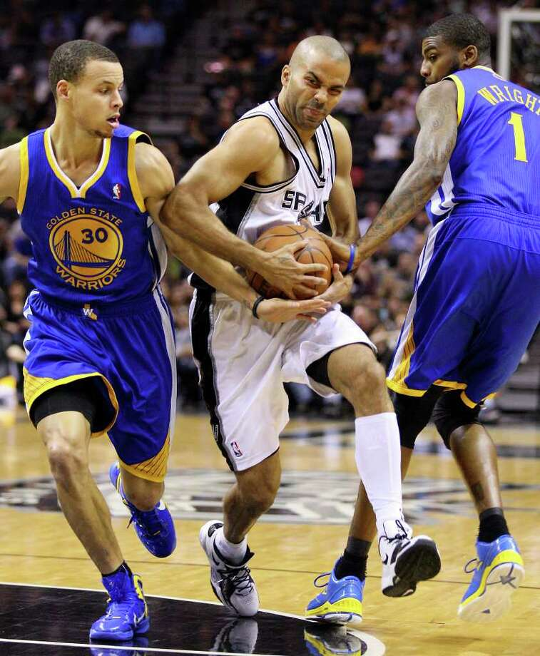 FOR SPORTS - Spurs' Tony Parker looks for room between  Warriors' Stephen Curry (left) and Warriors' Dorell Wright during first half action Monday March 21, 2011 at the AT&T Center.  (PHOTO BY EDWARD A. ORNELAS/eaornelas@express-news.net) / SAN ANTONIO EXPRESS-NEWS NFS