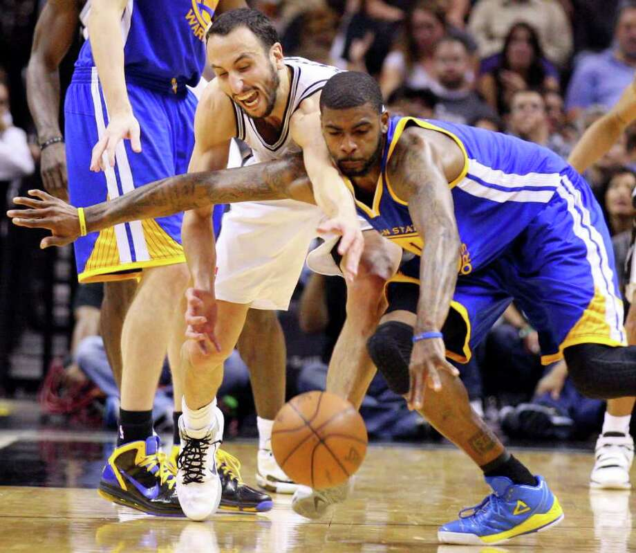 FOR SPORTS - Spurs' Manu Ginobili and  Warriors' Dorell Wright grab for a loose ball during second half action Monday March 21, 2011 at the AT&T Center. The Spurs won 111-96.  (PHOTO BY EDWARD A. ORNELAS/eaornelas@express-news.net) / SAN ANTONIO EXPRESS-NEWS NFS