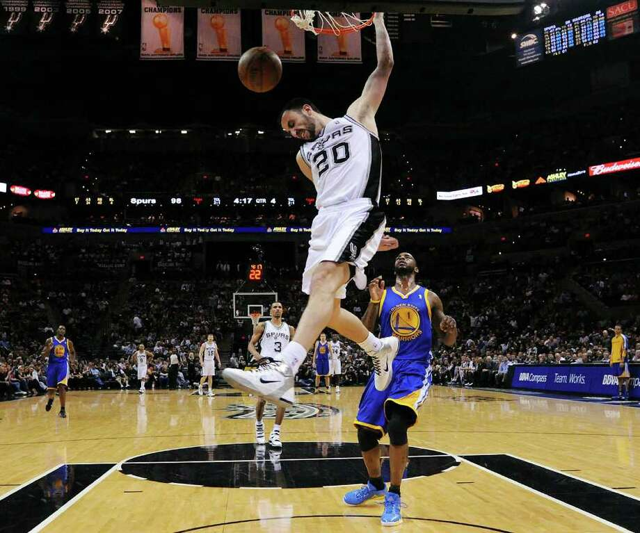 FOR SPORTS - Spurs' Manu Ginobili dunks as  Warriors' Dorell Wright looks on during second half action Monday March 21, 2011 at the AT&T Center. The Spurs won 111-96.  (PHOTO BY EDWARD A. ORNELAS/eaornelas@express-news.net) / SAN ANTONIO EXPRESS-NEWS NFS