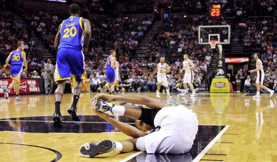 FOR SPORTS - Spurs' Tim Duncan holds his left foot after he sprained his left ankle against the Warriors during first half action Monday March 21, 2011 at the AT&T Center.  (PHOTO BY EDWARD A. ORNELAS/eaornelas@express-news.net) / SAN ANTONIO EXPRESS-NEWS NFS