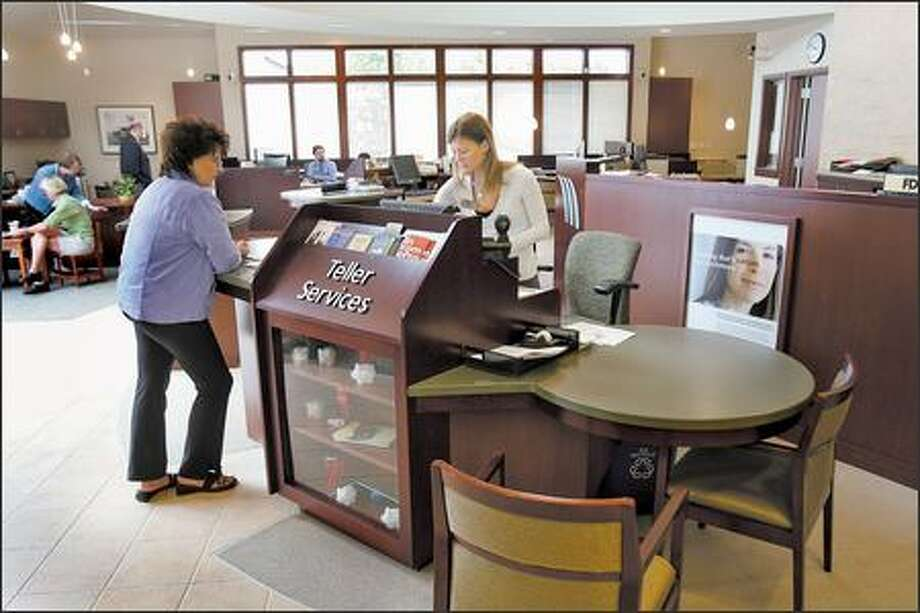 "Nerissa Hallberg, a teller at First Mutual Bank in Seattle helps a customer from her ""pod"" Tuesday. The pods, allowing a teller the ability to escape, are one of a number of new bank security measures designed to discourage potential bank robbers. Photo: Mike Urban/Seattle Post-Intelligencer"