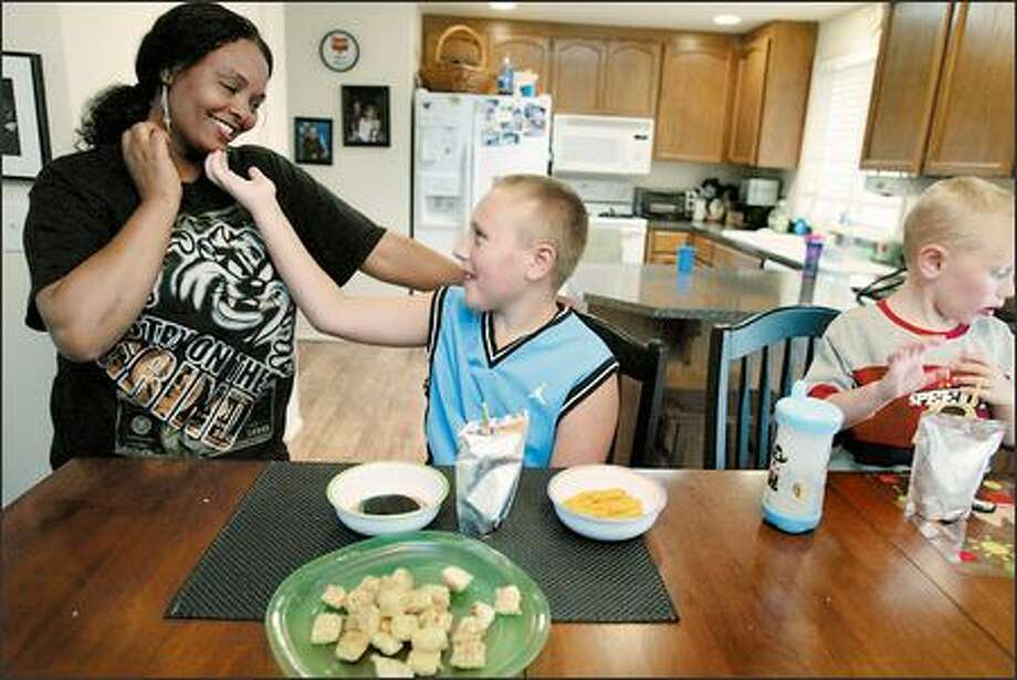 Nigsti Tewolde has taken care of 9-year-old Jordan Church, who is severely autistic, for three years. Jordan's mom, Kelly Church, worries that changes in the way the state approves home-care agencies may end their relationship. Jordan lives with his family, including his 3-year-old brother, Lucas, in Lynnwood. Photo: Paul Joseph Brown/Seattle Post-Intelligencer