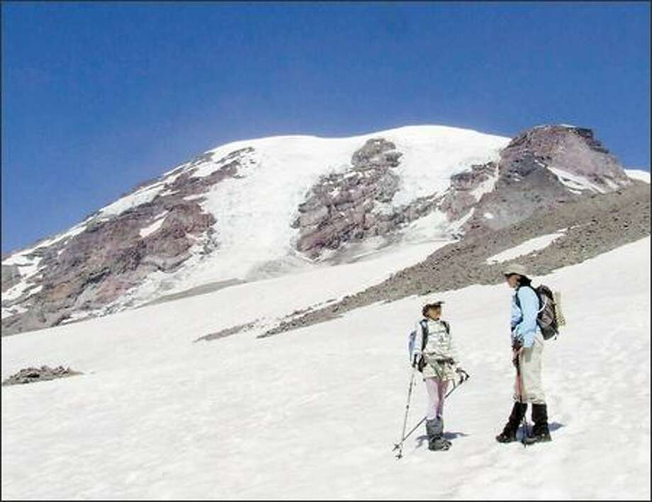 Bronka Sundstrom, left, and Barbara Eller take a break on the Muir Snowfield below 10,080-foot Camp Muir. In the background, the Nisqually Glacier cascades off the summit of Mount Rainier. Photo: KAREN SYKES