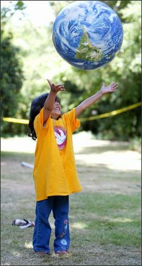 Aliyah Alothaimeen, 5, catches an inflatable globe during Middle East Peace Camp at the home of local peace activist and philanthropist Kay Bullitt on Wednesday, Photo: Joshua Trujillo/Seattle Post-Intelligencer