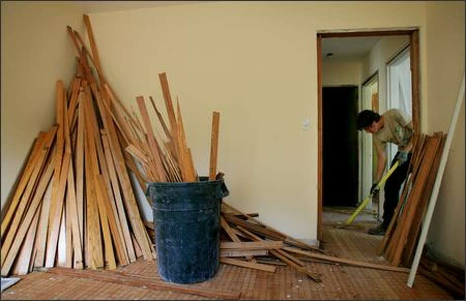 Jonathon Eaton of RE Store removes oak flooring last week from a house in the Bryant neighborhood. The wood will be bundled and resold to add beauty to a different house -- and keep it out of a landfill. Photo: Dan DeLong/Seattle Post-Intelligencer