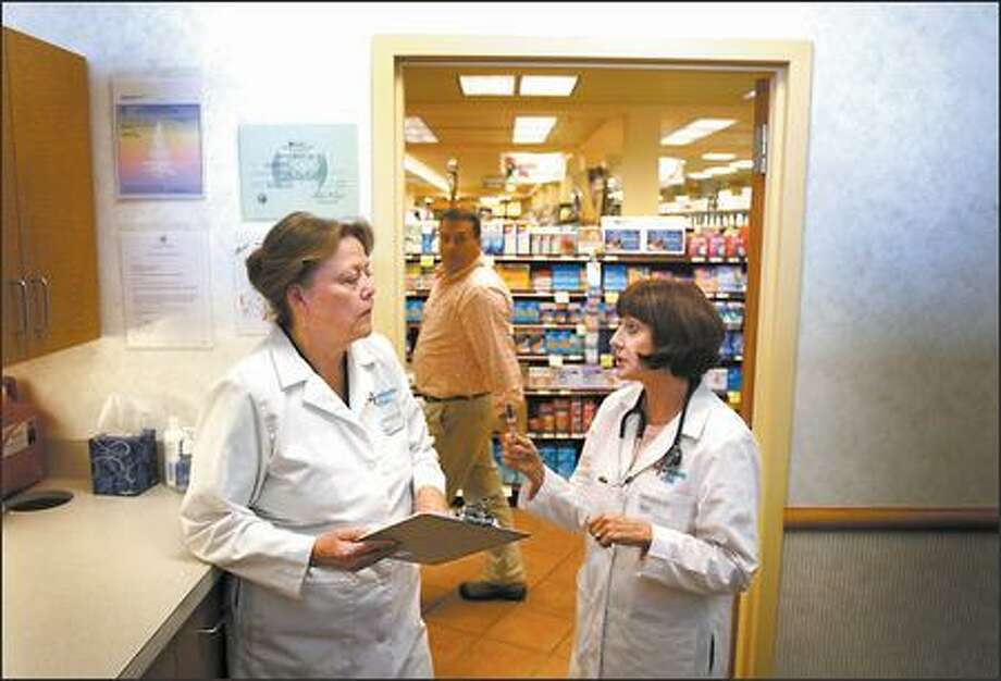 MinuteClinic manager Barbara Boardman, left, and nurse practitioner Diana Lachman discuss patients who visited the health clinic Tuesday. The clinic, which is inside the University Village QFC, says it averages five to 10 patients a day. Photo: Joshua Trujillo/Seattle Post-Intelligencer