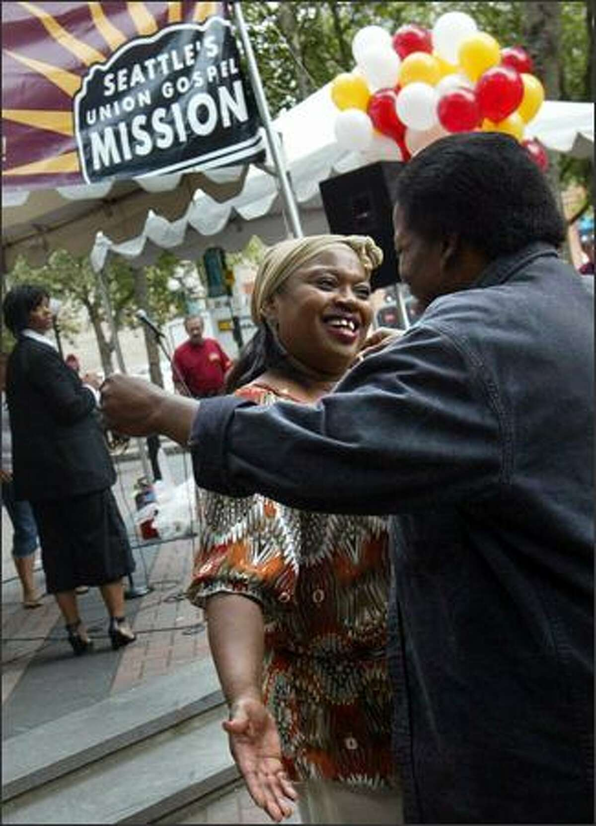 Gospel singer Josephine Howell hugs Raama Hunter at the Union Gospel Mission's 75th anniversary celebration Tuesday at Occidental Park. During her performance, Howell spoke about how she lived on the streets with her children for five years until she discovered the Union Gospel Mission.