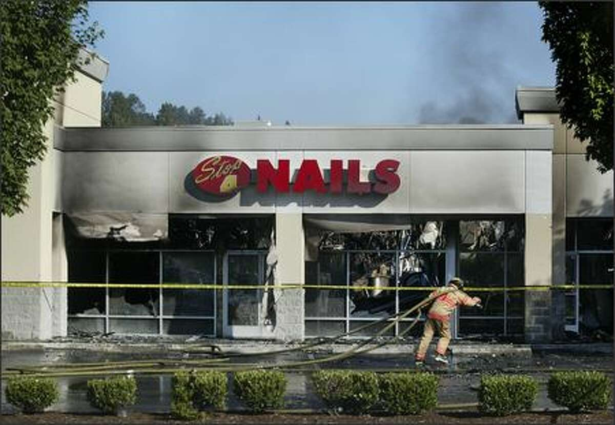 Smoke rises from the scene of an early morning fire that destroyed four businesses in a strip mall along Rainier Avenue South in Renton.