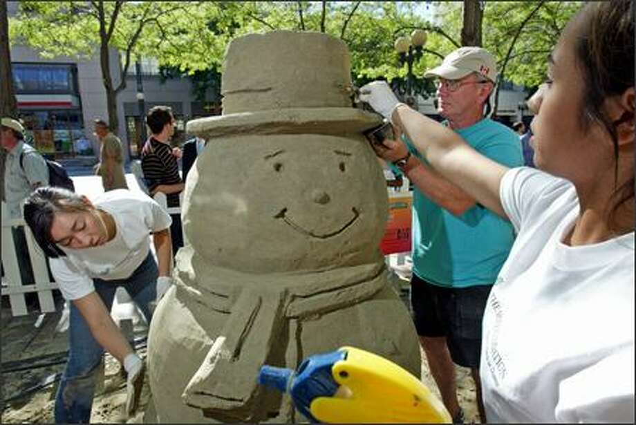 """""""Toasty the Sandman"""" gets a little help from his friends as they prepare for Seattle Sandfest at Westlake Center Park . On the left is Cari Anderson and her sister, Daron Anderso,n is on the right. Center is Vern Cooley, a master scupltor who was on hand when Toasty's brim fell off and needed to be repaired. Photo: Karen Ducey/Seattle Post-Intelligencer"""