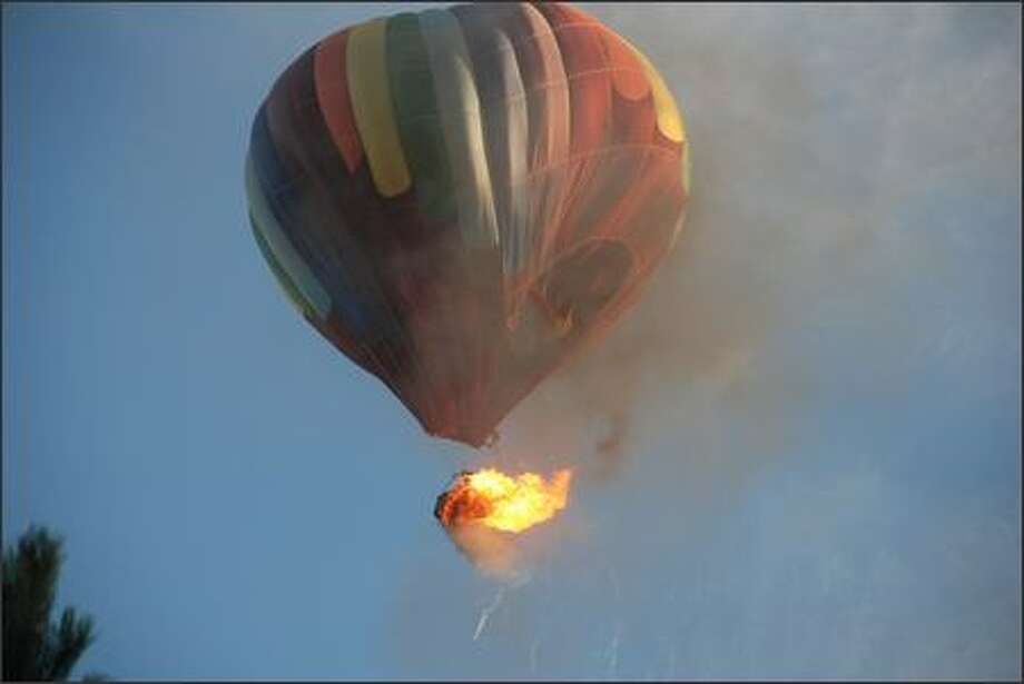 A hot air balloon's basket bursts into flames shortly after takeoff when it was about 25 feet off the ground in Surrey, B.C., on Friday evening.  (AP Photo/Don Randall) Photo: / Associated Press
