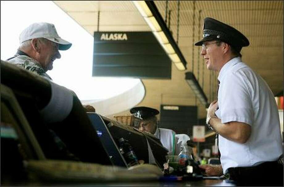 Skycap James Taggart jokes with Patrick O'Hanlon of Long Island, N.Y., Friday as O'Hanlon checks his bags. Taggart has worked at Sea-Tac Airport for 23 years. Photo: Dan DeLong/Seattle Post-Intelligencer