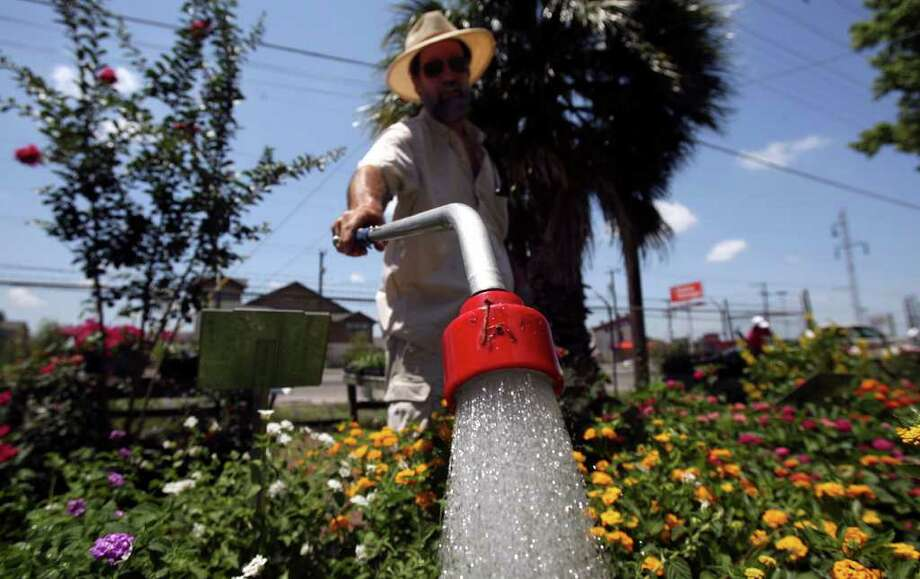 Burt Oatman waters flowers last summer at The Grove nursery on Austin Highway. Under Stage 1 restrictions, hand watering with a hose, soaker hose, drip irrigation, bucket or watering can is permitted at any time. Photo: JOHN DAVENPORT, John Davenport/Express-News / jdavenport@express-news.net