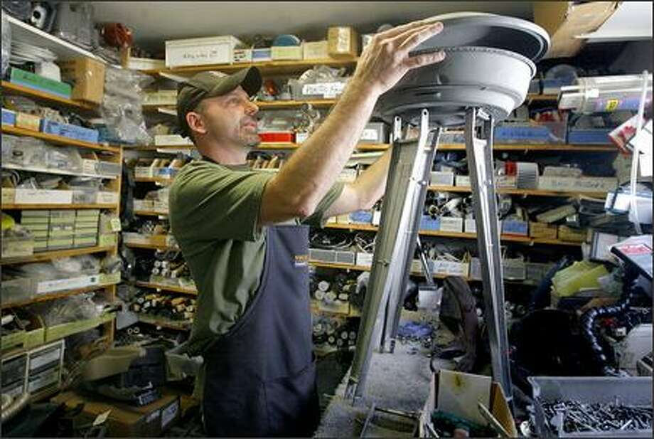 Will Flannery works on his latest creation -- a model of the Space Needle -- at The Vac Shop. Flannery, self-proclaimed vacuum artist and manager of the shop, has made robots, animals and spaceships out of discarded vacuum cleaners. Photo: Gilbert W. Arias/Seattle Post-Intelligencer