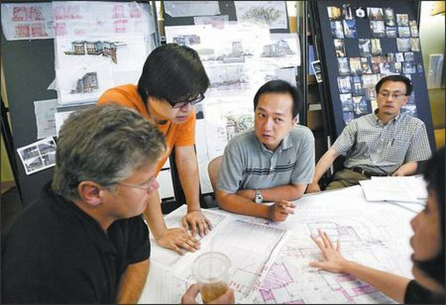 The international group at Mulvanny G2 Architecture discusses a project at its Bellevue office. MG2 is one of many companies hoping to capitalize on China's growth. Photo: Andy Rogers/Seattle Post-Intelligencer