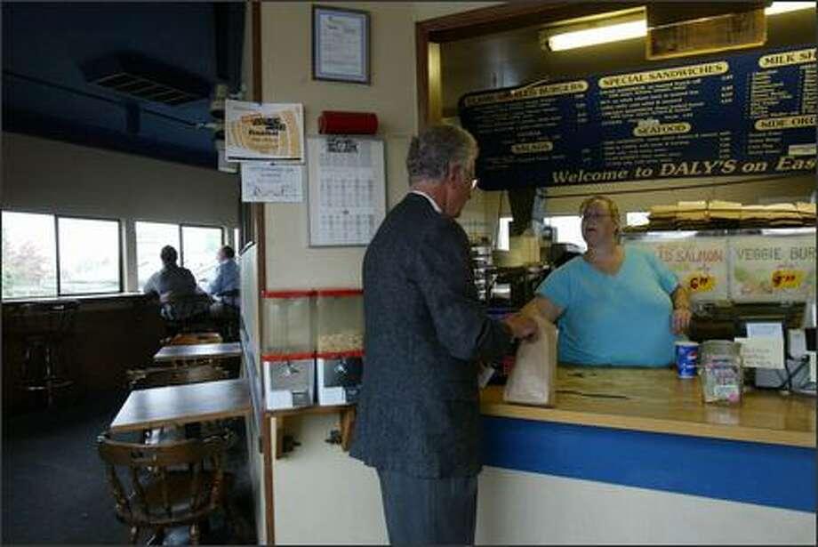 Customer Joe Kessler picks up his order from Maribeth Lewis at Daly's Drive-In in Eastlake on Tuesday. Photo: Karen Ducey/Seattle Post-Intelligencer