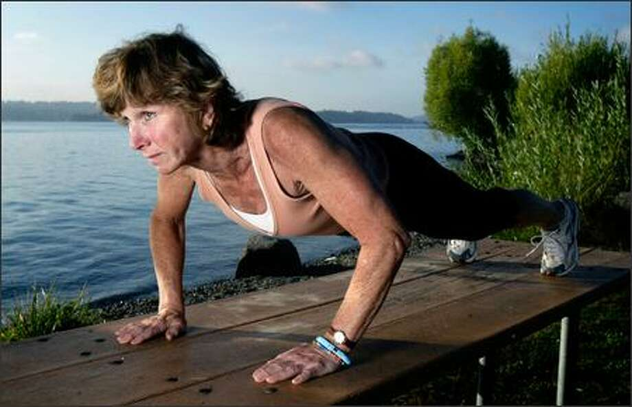 """Victoria Scott, a Seattle personal trainer and triathlete, demonstrates a perfect-form push-up, keeping her body in a """"straight line, no rear end way up in the air."""" Photo: Andy Rogers/Seattle Post-Intelligencer"""