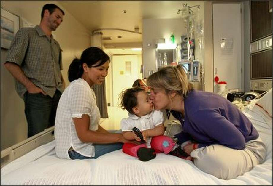 Kristina Southard, who was diagnosed with a rare bone-marrow cancer, plants a kiss on 10-month-old Ella Heverley, who is visiting with parents Chad and Jina Heverley at Virginia Mason. After Southard has a bone-marrow transplant and is released from the hospital, she will need 24-hour care for the first few months. Photo: Mike Urban/Seattle Post-Intelligencer