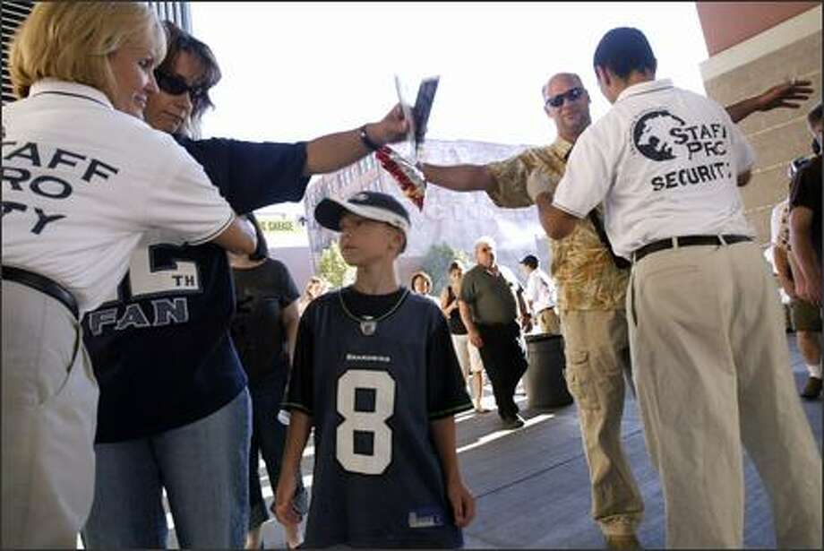 As her son Grant, 7, looks on, Leslie Neighbor, left, is searched by Qwest Field security personnel before the Seahawks-Raiders game Aug. 30. Photo: Andy Rogers/Seattle Post-Intelligencer