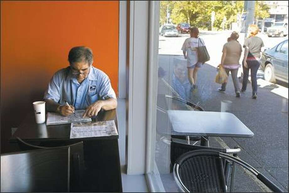 Postal worker Michael Menaglia takes a break Monday at Cafe Javasti in Wedgwood. Menaglia said the changes to the neighborhood are not going to be good. Photo: Gilbert W. Arias/Seattle Post-Intelligencer