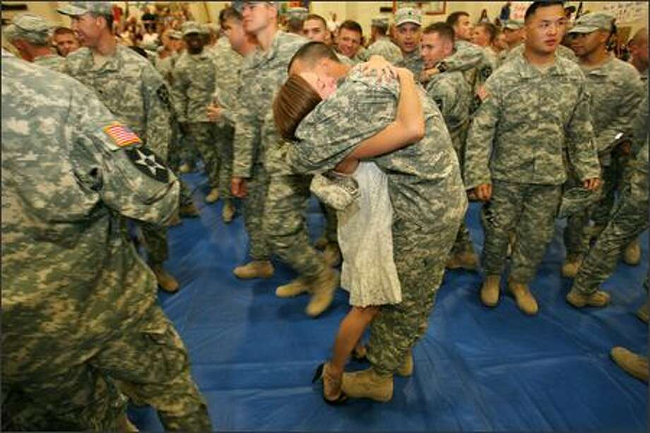 Jennifer Brown is embraced by her husband Specialist Jason Goozvat within a sea of green camouflage members of the Stryker Brigade. Photo: Mike Urban/Seattle Post-Intelligencer