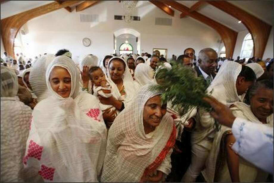At the end of a 5 hour service, (left) Mesert Tesfaye, Yeshawal Zeleke (with baby) and local Ethiopians are blessed for the new millennium with holy water applied with a mixture of herbs (rue and rosemary), at St. Gebriel Church in Seattle. Photo: Meryl Schenker/Seattle Post-Intelligencer