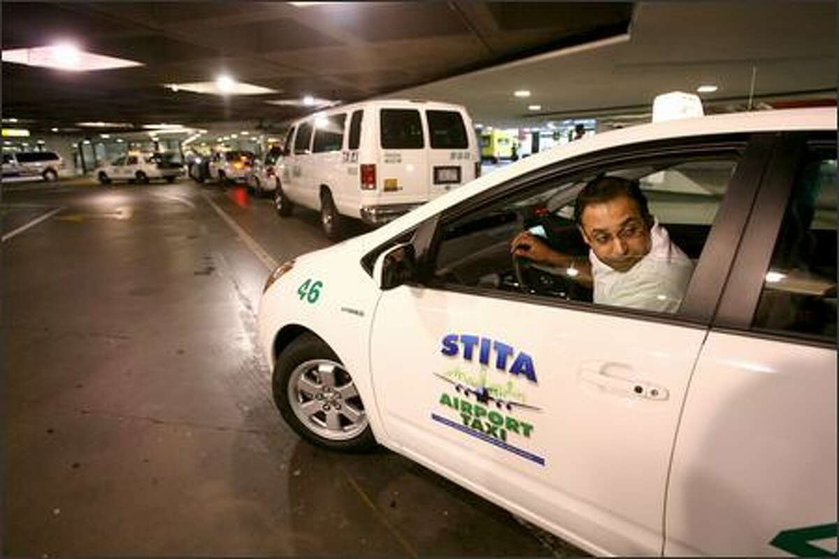 Taxi driver Karambir Sangha checks the blind spot as he pulls out driving one of the first hybrid cabs in the Seattle area.