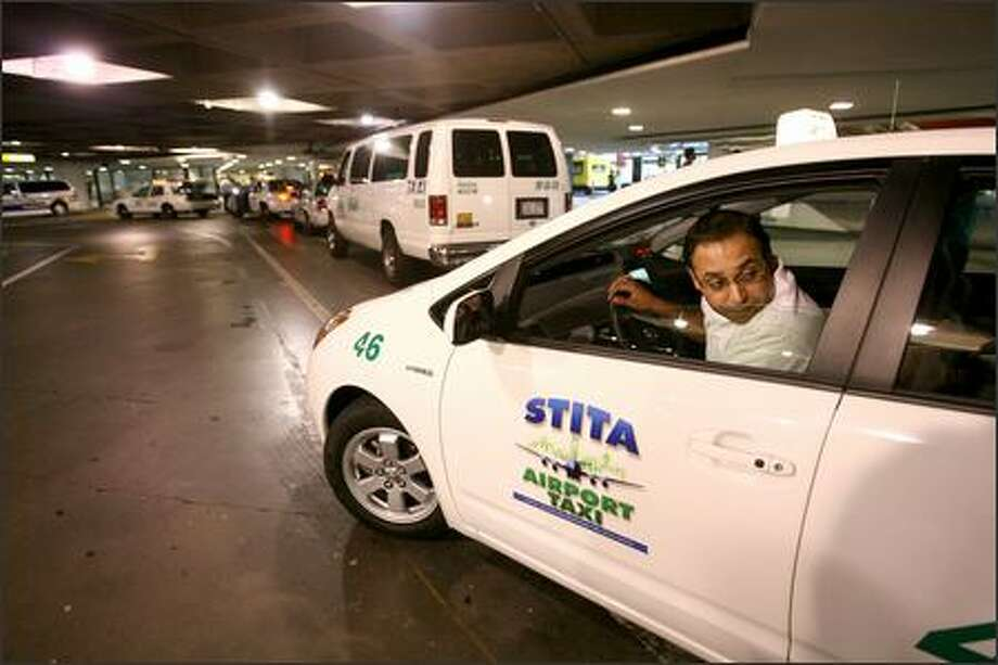 Taxi driver Karambir Sangha checks the blind spot as he pulls out driving one of the first hybrid cabs in the Seattle area. Photo: Scott Eklund/Seattle Post-Intelligencer